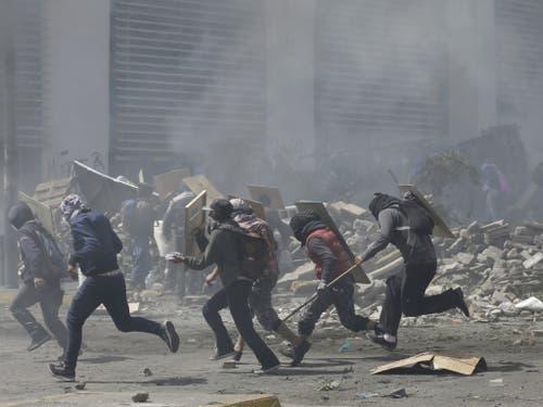 Protestierende Regierungsgegner flüchten am Samstag in Quito vor dem Tränengas der Polizei. (Bild: Keystone/AP/FERNANDO VERGARA)