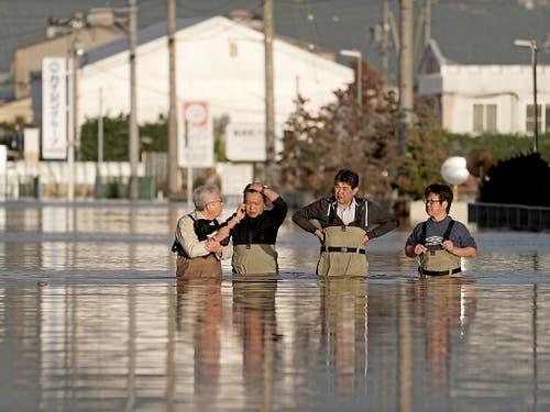 In Nagano stehen Angestellte einer Firma im Hochwasser, um den Zustand ihres Büros (nicht im Bild) zu prüfen. Die Provinz Nagano war am stärksten von Überschwemmungen betroffen, nachdem der Chikuma-Fluss durch die Uferdämme gebrochen war. (Bild: KEYSTONE/EPA/KIMIMASA MAYAMA)