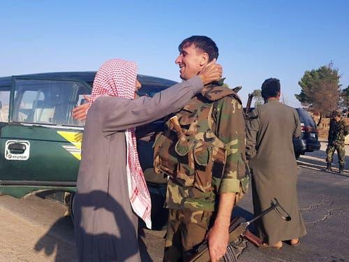 Syrische Regierungstruppen haben in Kurdengebieten nahe der Grenze zur Türkei Stellung bezogen. Sie wurden in der Stadt Tall Tamar nordwestlich von Al-Hassaka von Einwohnern begrüsst. (Bild: KEYSTONE/EPA SANA/SANA HANDOUT)