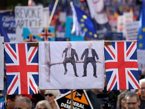 Der britische Premier Boris Johnson und der Brexit-Partei-Chef Nigel Farage, die sich den eigenen Ast absägen - Protestplakat der Brexit-Gegner. (Bild: KEYSTONE/AP/MATT DUNHAM)