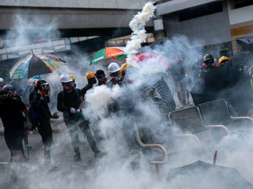 Sicherheitskräfte setzten am Dienstag in Hongkong erneut Tränengas ein und schossen sogar auf Demonstranten. (Bild: KEYSTONE/EPA/JEROME FAVRE)
