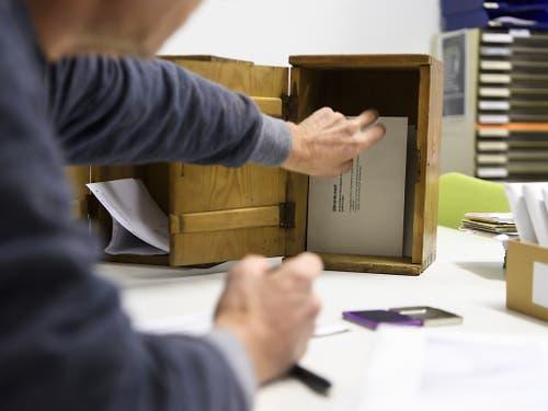 Nach Schliessung des Wahllokals holt ein Wahlhelfer die Stimmcouverts aus der Urne. (Bild: KEYSTONE/ANTHONY ANEX)