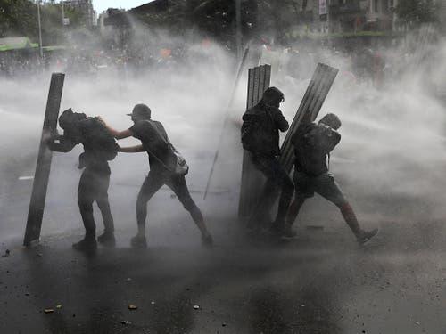 Demonstranten schützen sich in der chilenischen Hauptstadt Santiago vor Wasserwerfern der Polizei. Der Präsident des Landes hat nun auf die Kundgebungen reagiert und Reformen angekündigt. (Bild: KEYSTONE/AP/RODRIGO ABD)
