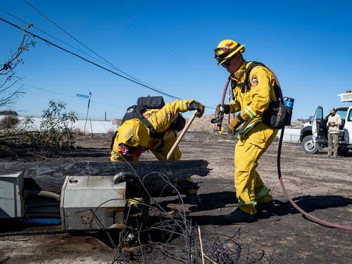 Feuerwehrleute untersuchen einen bei einem Buschfeuer umgestürzten Strommasten bei Santa Clarita in Kalifronien. (Bild: KEYSTONE/AP FR 171731/CHRISTIAN MONTERROSA)
