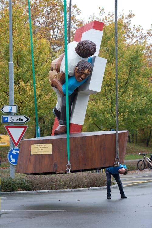 Bildhauer Stephan Schmidlin kontrolliert, ob seine Skulptur auch richtig befestigt ist. (Bild: Maria Schmid, Zug, 30. Oktober 2019)