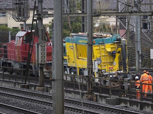 Ein Schienentraktor zieht den Bahnflachwagen mit dem Sauglaster. (Bild: KEYSTONE/PETER KLAUNZER)