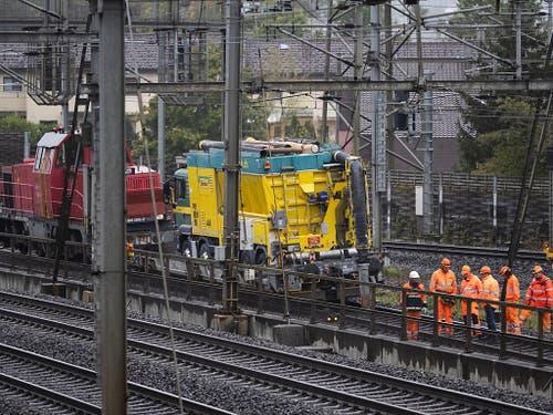 Der ölverschmutzte Schotter muss weg: Der gelbe Sauglastwagen fährt die verunreinigten Geleise Meter für Meter ab. (Bild: KEYSTONE/PETER KLAUNZER)