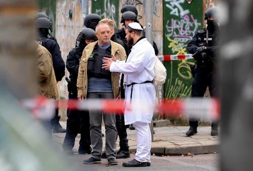 Ein Besucher einer Synagoge spricht mit der Polizei in Halle. (Bild: EPA/FILIP SINGER)
