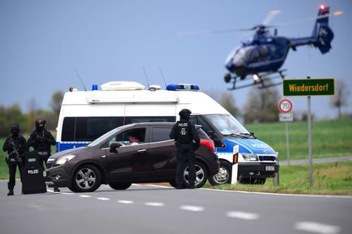 Polizeieinheiten blockieren eine Strasse in der Nähe von Wiedersdorf bei Landsberg, (Bild: EPA/CLEMENS BILAN)