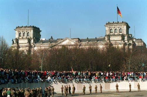 Deutsche aus dem Westen und Osten stehen auf der Mauer vor dem Reichstagsgebäude. (Bild: Keystone / AP, 9. November 1989)