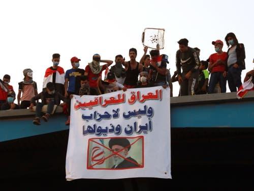 «Irak den Irakern und nicht den iranischen Parteien und ihren Ausläufern» steht auf dem Transparent in Bagdad mit dem Bild des iranischen geistlichen Oberhaupts Ayatollah Ali Chamenei. (Bild: KEYSTONE/EPA/AHMED JALIL)