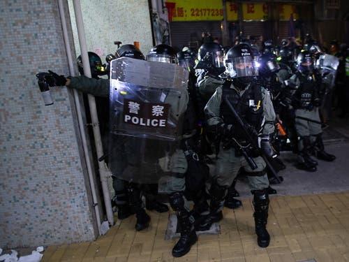Ein Hongkonger Polizist setzt bei Auseinandersetzungen mit Demonstranten Pfefferspray ein. (Bild: KEYSTONE/EPA/JEROME FAVRE)