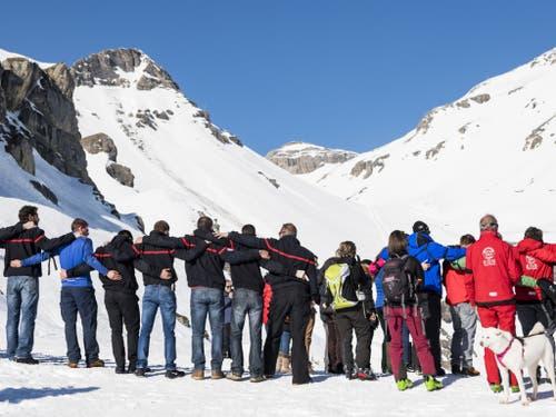 Angehörige, Mitarbeiter der Bergbahnen und Passanten versammeln sich für eine Schweigeminute zu Gedenken des Lawinenopfers. (Bild: Keystone/JEAN-CHRISTOPHE BOTT)