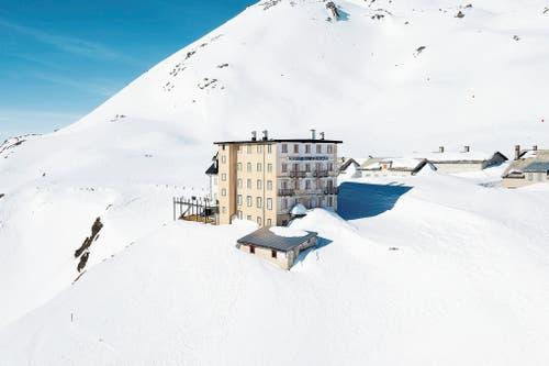 Ungefähr so präsentiert sich das Hotel Furkablick derzeit. Abgesehen von den 8,7 Zentimeter breiten Streifen an den Fensterläden (von Daniel Buren) ist die Kunst noch im Schnee verborgen. (Bild: Christof Hirtler)