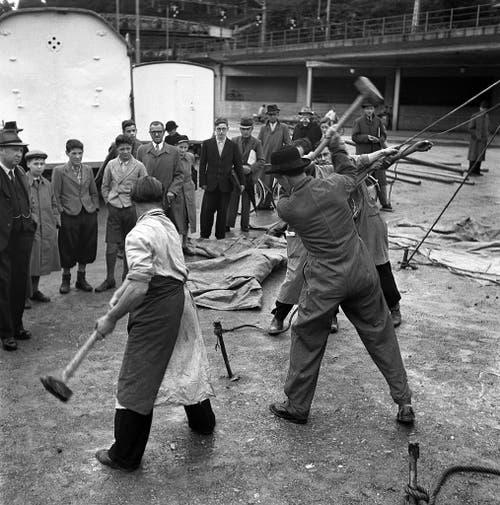 Zuschauer beobachten, wie Mitarbeiter des Zirkus Knie einen Hering für die Zeltseile einschlagen. (Bild: Keystone /Str)