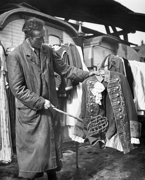 Ein Mitarbeiter des Zirkus Knie klopft im Winterquartier in Rapperswil den Staub aus einer reich verzierten Uniform, undatierte Aufnahme. (Bild: Keystone /Str)