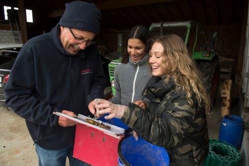 Die Schülerinnen Jil Weingartner (links) und Eniza Iten sammeln bei Sempach die Amphibien ein und setzen sie später beim Steinibühlweiher wieder aus. Zusammen mit Experte Josef Blum werden die Tiere bestimmt, gezählt und erfasst. (Bild: Dominik Wunderli, 15. März 2019)