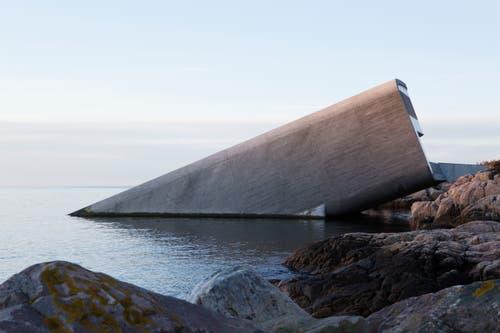Vom Gebäude ist vom Land aus lediglich der Eingangsbereich sichtbar; das Ganze sieht aus, als wenn ein Tunnelelement oder ein Flugobjekt mit abgerundeten Kanten ins Meer eingetaucht wäre. (Bild: PD/Snöhetta)