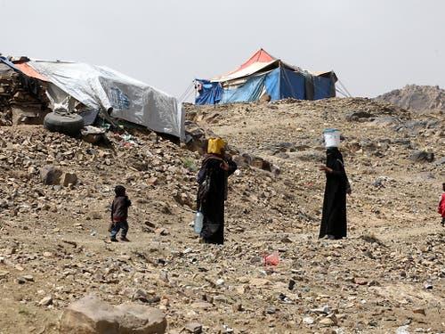 Frauen tragen Wasser in ihr behelfsmässiges Flüchtlingslager im Jemen. (Bild: KEYSTONE/EPA/YAHYA ARHAB)
