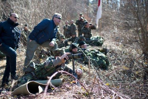 Unter der fachkundigen Beobachtung von Polizeikommandant Armbruster (ganz links im Bild) und Markus Ming von der Offiziersgesellschaft Zug schiessen die Scharfschützen auf Zielscheiben auf der anderen Seite des Tals.