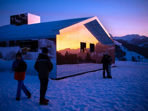 Spaziergänger auf dem Winterwanderweg zwischen Gstaad und Schönried sehen sich die Installation des amerikanischen Küstlers Doug Aitken an. (Bild: KEYSTONE/ANTHONY ANEX)