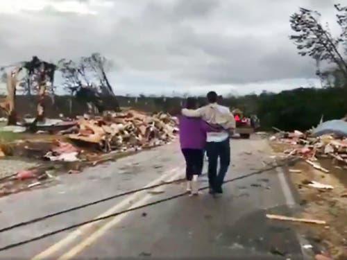 Kleinholz: Menschen laufen durch die Trümmer eines mutmasslichen Tornados in Lee County im US-Bundesstaat Alabama. (Bild: KEYSTONE/AP WKRG-TV)