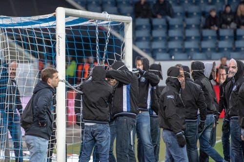 Die Ultras verketten das Tor. Der Grossteil der Beteiligten versteckt das Gesicht hinter einer Maske. Ohne Maske auf dem Bild ist ein Fanarbeiter des FCL. (Bild: Keystone/Urs Flüeler, Luzern, 7. März 2019)