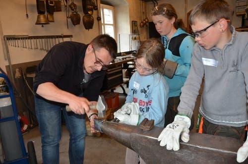 Kursleiter Raphael Gygax zeigt den Kindern, wie genietet wird.