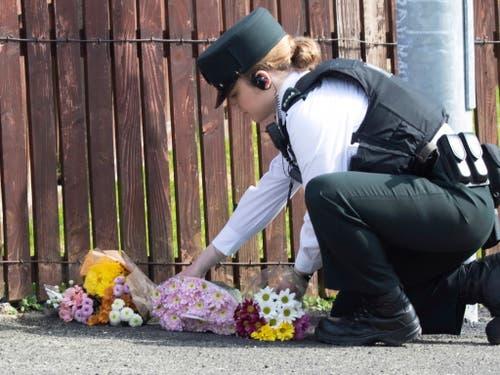 Eine Polizistin legt Blumen nieder, wo die Journalistin Lyra McKee von einer Kugel getroffen wurde und starb. Die Ordnungshüter vermuten, dass katholische Extremisten hinter der Tat stehen. (Bild: KEYSTONE/EPA/JOE BOLAND / NORTH WEST NEWSPIX)