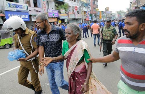 Männer helfen einer älteren Frau in der Nähe von einem der Explosionsorte in der Hauptstadt Colombo.