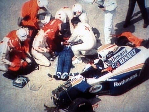 Sicherheitskräfte versuchen Ayrton Senna zu helfen - vergeblich. Am Abend des Unfalltags wurde der Tod der Ikone verkündet (Bild: KEYSTONE/AP TV TOKYO)