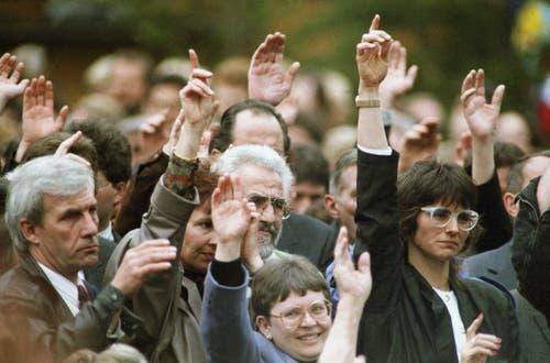 Erstmals heben an der Innerrhoder Landsgemeinde von Appenzell Bürgerinnen und Bürger zur Abstimmung gemeinsam die Hand. (Bild: 28. April 1991, Keystone/Str)