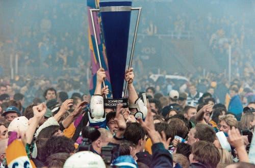 Vor fast genau 21 Jahren: Umringt von Fans stemmt Zug-Stürmer Stefan Grogg den Meisterpokal in die Höhe. (Bild: Arno Balzarini/Keystone, Davos, 11. April 1998)