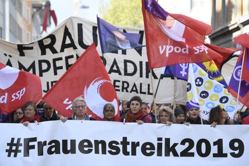Kundgebungsteilnehmer laufen in Zürich im Zeichen des Frauenstreiks. (KEYSTONE/Ennio Leanza)