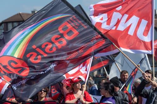 Fahnen der Gewerkschaften Unia und Basis 21 am Demonstrationszug in Basel. (KEYSTONE/Georgios Kefalas)