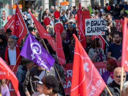 Am Tag der Arbeit sind etwa in Genf neben den roten auch violette Fahnen im Umzug zu entdecken. Sie stehen für die Forderungen nach Lohngleichheit zwischen Mann und Frau. (Bild: KEYSTONE/MARTIAL TREZZINI)