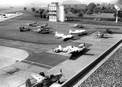 Blick auf den Militärflugplatz Emmen im Jahr 1962. Auf dem Bild zu sehen sind eine Pilatus P-2 und P-3, AT-16, C-36, Brücker Bü-133, Pilatus PC-6 «Porter »und im Hintergrund links eine DH-112 «Venom». (Bild: VBS)
