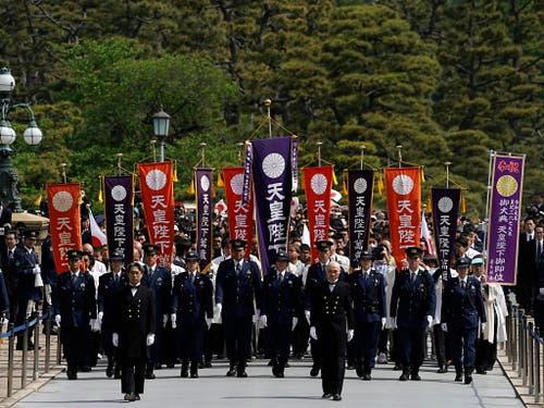 Auf dem Weg in den kaiserlichen Palast: Polizisten marschieren vor Gratulanten mit Fahnen. (Bild: KEYSTONE/EPA/FRANCK ROBICHON)