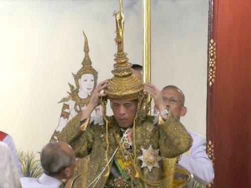 Der feierliche Moment: Thailands König Maha Vajiralongkorn setzt sich auf dem Thron sitzend die Krone auf. (Bild: KEYSTONE/AP Thai TV Pool)