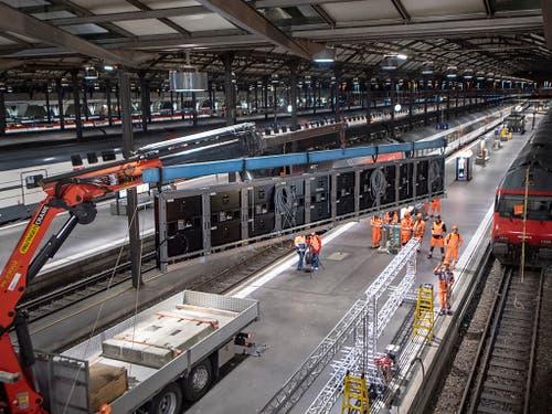 Ein Kran hievt die Anzeigetafeln bei der Stirn des Luzerner Bahnhofs zur Montage in die Höhe. (Bild: KEYSTONE/URS FLUEELER)