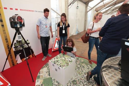 Leonie Szarka (Lernende) bei der Trigonet AG und Jochen Veitinger zeigen der kleinen Besucherin den Stand. (Bild: Roger Zbinden, 1. Juni 2019)
