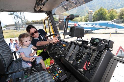 Helen Burri von der Pilatus-Betriebsfeuerwehr zeigt der kleinen Laura Meyer das Universal-Löschfahrzeug (ULF). (Bild: Roger Zbinden, 1. Juni 2019)