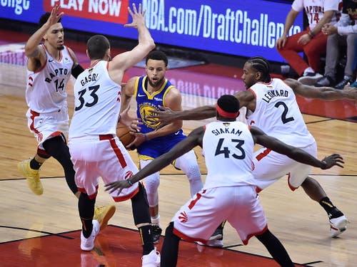 Umringt von gleich vier Spielern der Toronto Raptors sucht Golden States Topskorer Stephen Curry einen Ausweg. Mit 31 Punkten war er der beste Punktesammler der Warriors (Bild: KEYSTONE/EPA/LARRY W. SMITH)