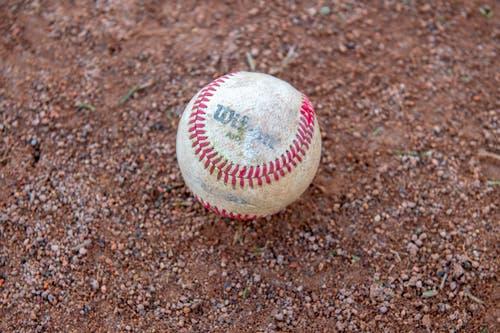 Baseball: Der zwischen 142 bis 149Gramm wiegende Ball ist von zwei weissen Lederstücken umhüllt, die mit roten Fäden zusammengenäht sind. Sein Inneres ist aus einem Korkkern und einem äusserst dicht darum gewickelten Faden zusammengesetzt.