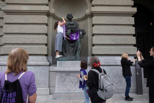 Eine Aktivistin hängt eine Fahne an eine Statue vor dem Bundeshaus. (Bild: KEYSTONE/Peter Klaunzer)