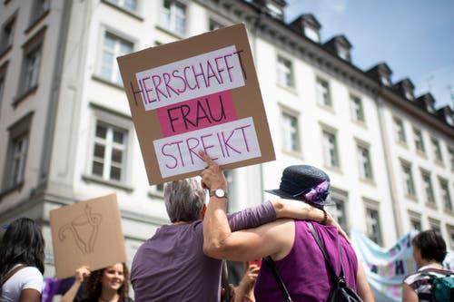 Zwei Frauen umarmen sich mit einem Plakat in der Hand, an einer Kundgebung zum nationalen Frauenstreik, am Freitag, 14. Juni 2019, in St. Gallen. (Bild: KEYSTONE/Gian Ehrenzeller)