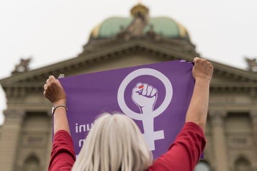 Eine Frau schwingt die Fahne des Frauenstreiks vor dem Bundeshaus, am Freitag, 14. Juni 2019 in Bern. (Bild: KEYSTONE/Alessandro della Valle)
