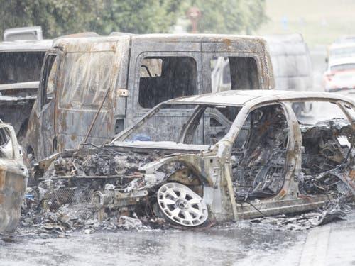 Die Wracks von mehreren ausgebrannten Fahrzeugen am Tatort in Mont-sur-Lausanne. (Bild: Keystone/CYRIL ZINGARO)