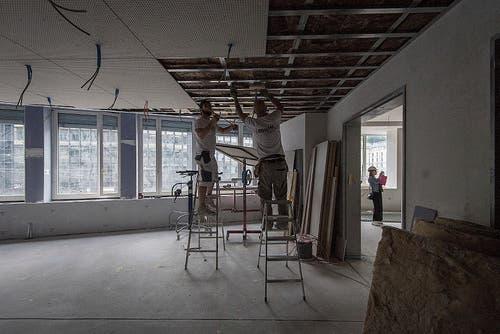 In den Seminarräumen bauen Arbeiter die Schallschutzdecke ein.
