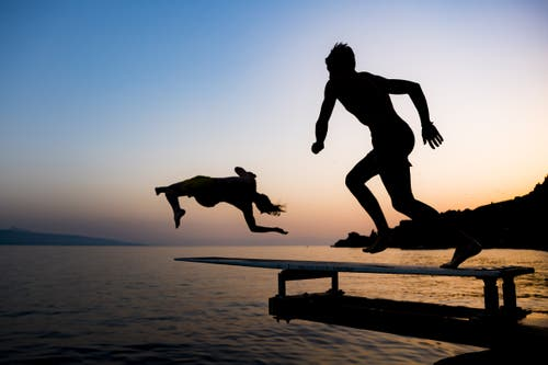 Zwei Personen springen bei Saint-Saphorin in den Genfersee. (Bild: Jean-Christophe Bott / Keystone, 26. Juni 2019)